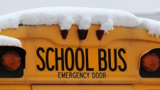 A school bus is covered in snow in this file photo. (The Indianapolis Star / Brent Drinkut)