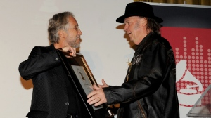 Academy President and CEO Neil Portnow, left, presents honoree Neil Young with a tribute plaque at the Producers and Engineers of The Academy's 7th Annual Grammy Week Event, at The Village Recording Studios, on Tuesday, Jan. 21, 2014, in West Los Angeles. (Photo by Frank Micelotta/Invision/AP)