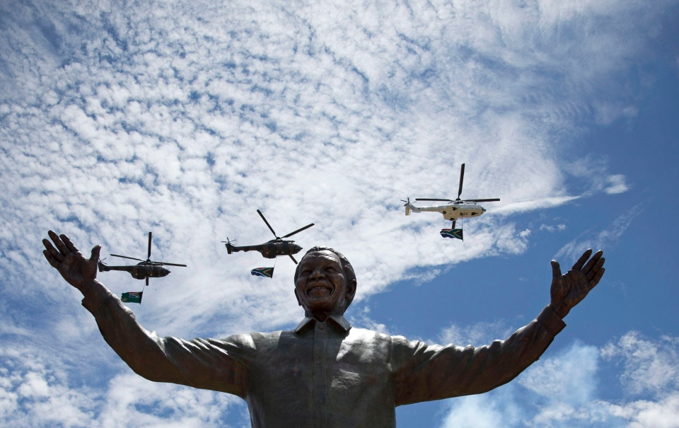 Helicopters perform a flypast as smoke rises from a gun salute after the unveiling of a 9-metre bronze statue of former South Africa President Nelson Mandela outside Union Buildings in Pretoria, South Africa, Monday, Dec. 16, 2013. (AP / Matt Dunham)