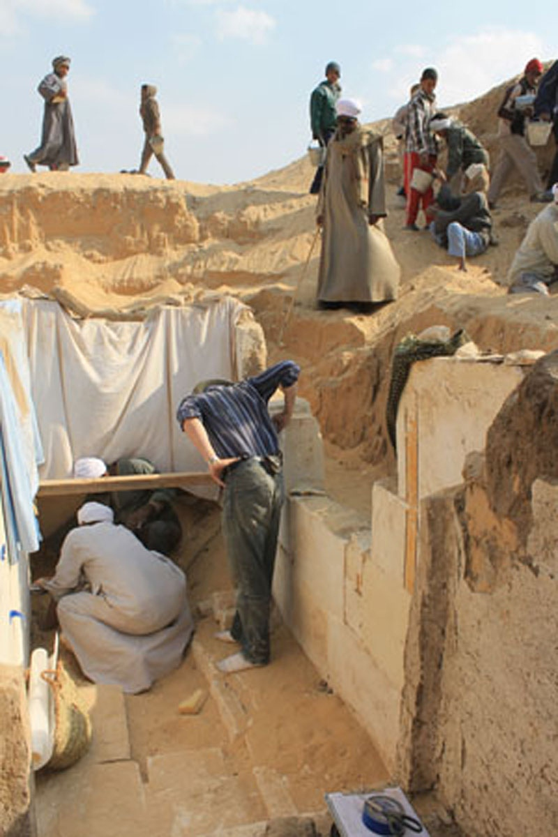 Team members work to excavate the burial chamber of the pharaoh Woseribre Senebkay, with sheets covering a painted wall decoration (Photo: Josef Wegner, Penn Museum)