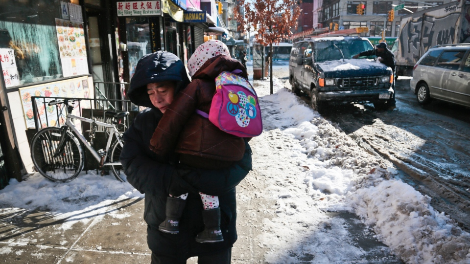 A child is lifted and carried along a snowy sidewalk, while snow is cleared off a van on Wednesday Jan. 22, 2014 in New York. A winter storm dumped a foot or more of snow, grounded flights and closed schools across much of the Northeast but not in New York City. (AP / Bebeto Matthews)