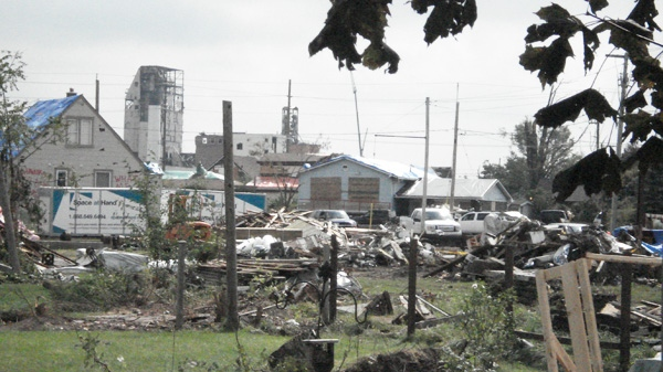Piles of debris cover the property of a Goderich lumber yard, while damaged homes and industrial buildings can be seen in the background, on on Saturday, Aug. 27, 2011. (Thom Leigh for CTVNews.ca)