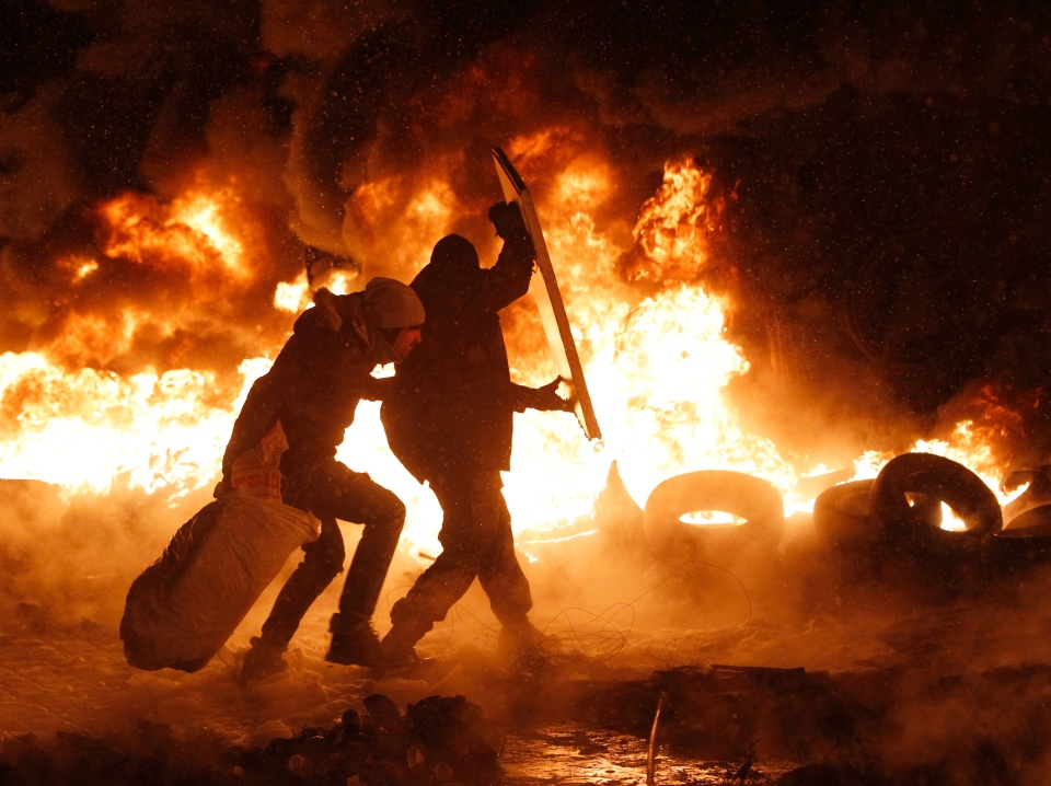 Protesters throw tires onto a fire during clashes with police in central Kyiv, Ukraine, Wednesday, Jan. 22, 2014. (AP / Sergei Grits)