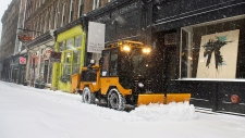 Snow plow clears sidewalk after a Halifax blizzard