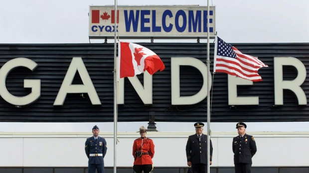The Canadian and United States flags were lowered to half mast at a commemorative ceremony to mark the first anniversary of the terrorist attacks against the U.S., in Gander, Nfld. on Wednesday, Sept. 11, 2002. (THE CANADIAN PRESS/Andrew Vaughan)