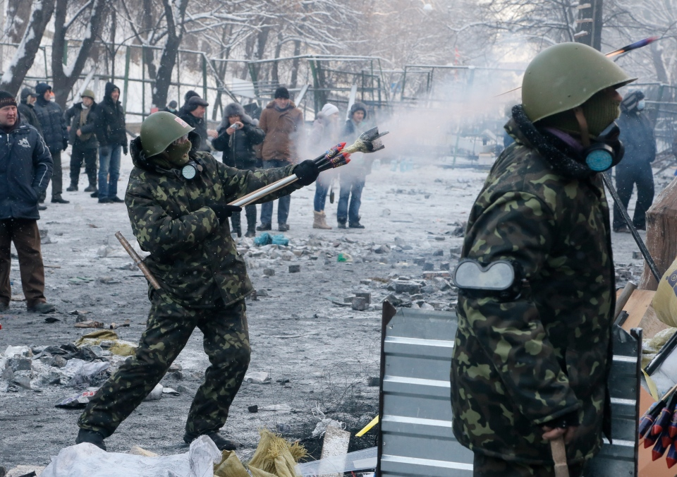 A protester aims fireworks at police during clashes, in central Kyiv, Ukraine, Thursday, Jan. 23, 2014. (AP Photo/Efrem Lukatsky)
