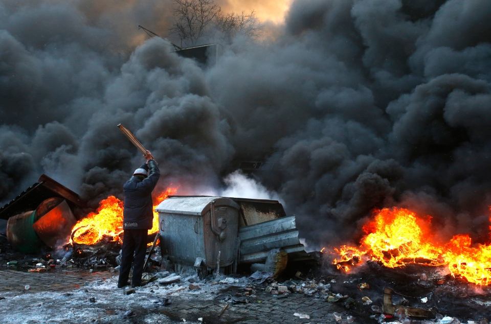 A protester beats a dumpster after clashes with police in central Kiev, Ukraine, Thursday Jan. 23, 2014. (AP / Sergei Grits)