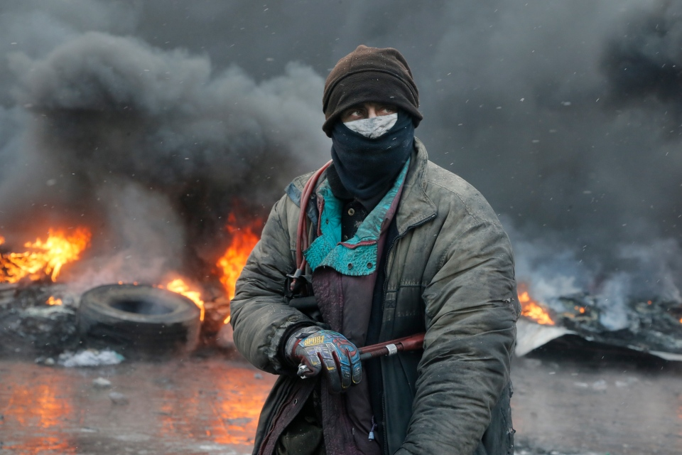 A protester stands at a burning barricades between police and protesters in central Kiev, Ukraine, Thursday Jan. 23, 2014. (AP / Efrem Lukatsky)