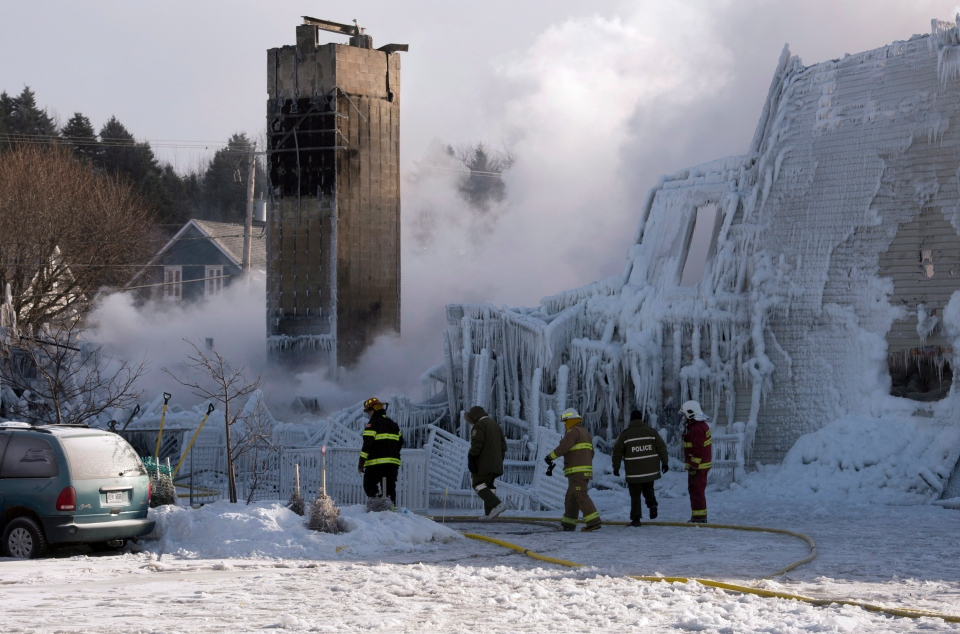 Firefighters work at the scene of a senior's residence fire in L'Isle-Verte, Que. on Thursday, Jan. 23, 2014. (Jacques Boissinot / THE CANADIAN PRESS)