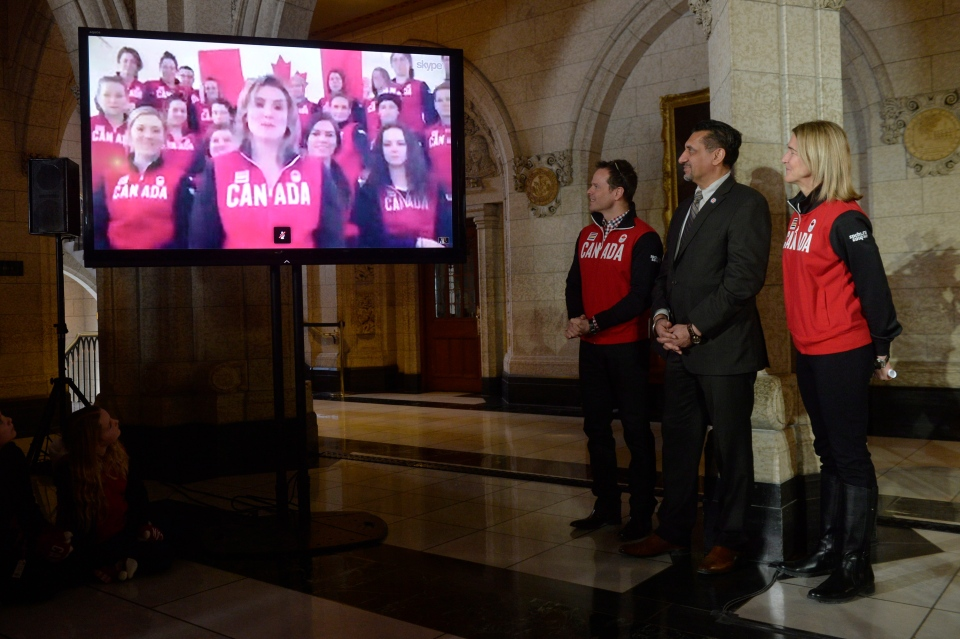 Hayley Wickenheiser, surrounded by members of the Canadian women hockey team, speaks from Austria through a video relay, in the foyer of the House of Commons in Ottawa, Thursday Jan. 23, 2014.  (Adrian Wyld / THE CANADIAN PRESS)
