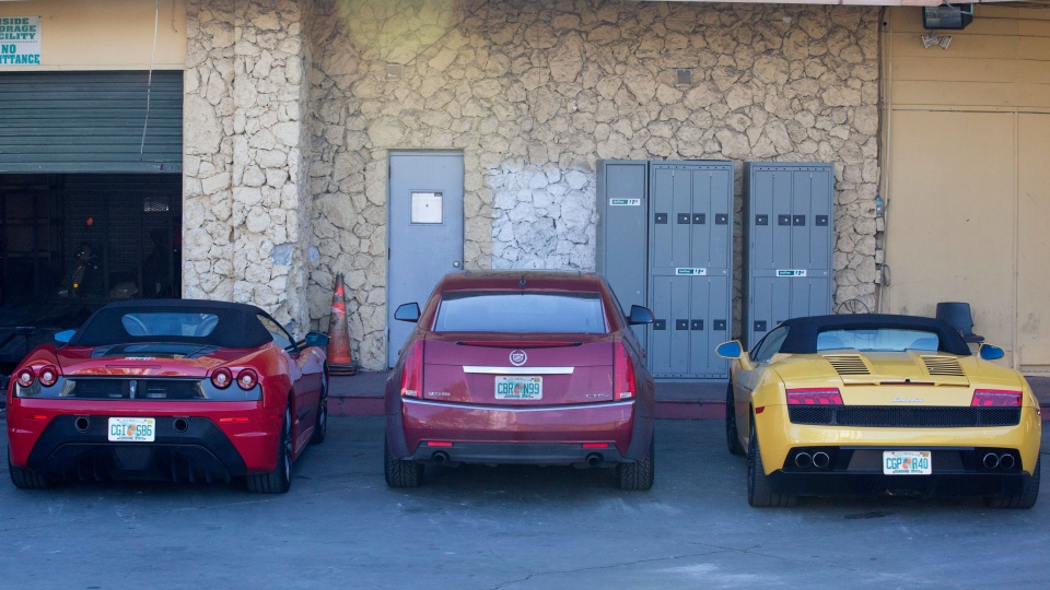 A Lamborghini, right, and a Ferrari, left, allegedly involved in a drag race are shown in an impound lot in Miami Beach, Fla, Thursday, Jan. 23, 2014. (AP / Wilfredo Lee)