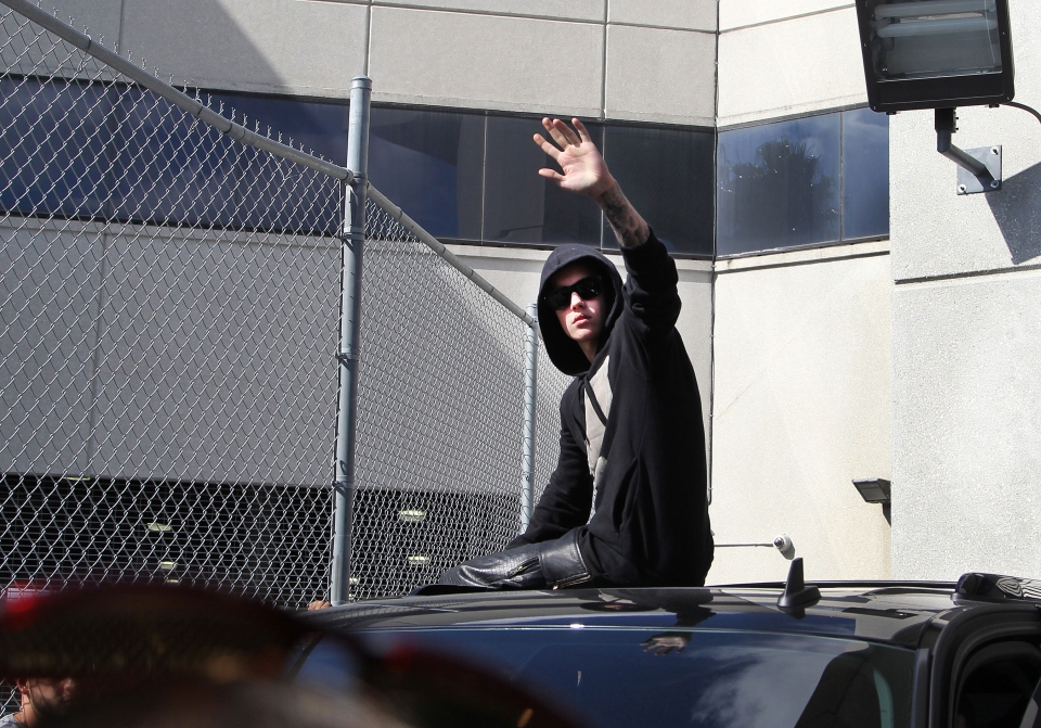 Justin Bieber waves from atop an SUV as he leaves the Turner Guilford Knight Correctional Centre in Miamai, Thursday, Jan. 23, 2014. (El Nuevo Herald / Hector Gabino)
