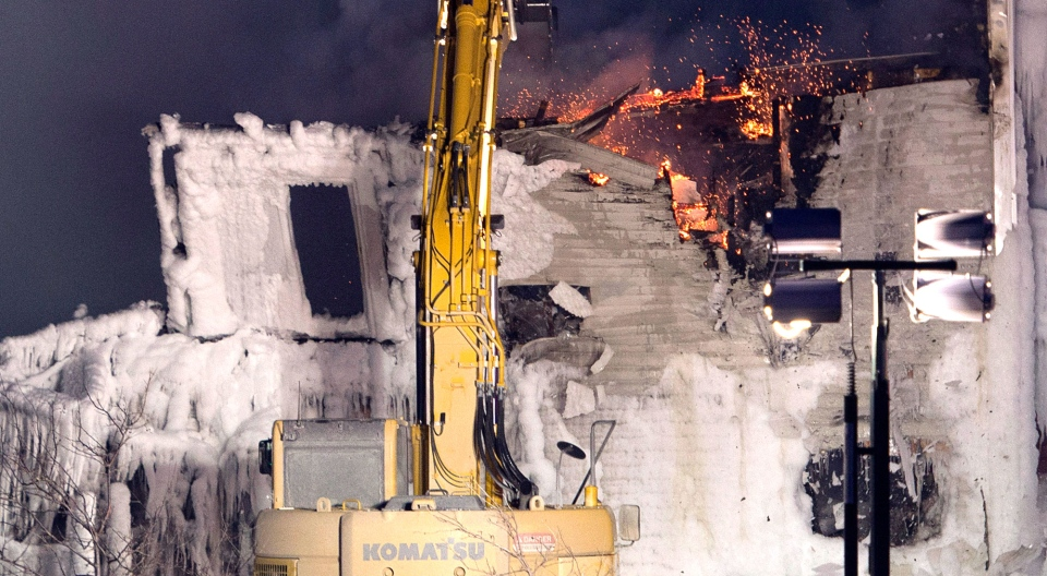 A crane knocks down a wall after a fatal fire destroyed a seniors residence in L'Isle-Verte, Que., Thursday, Jan. 23, 2014. (Ryan Remiorz / THE CANADIAN PRESS)