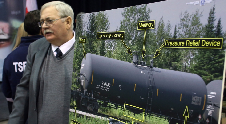 Donald Ross, senior investigator of rail and pipeline for the Transportation Safety Board, walks behind a display of tanker cars at a news conference in Ottawa, Thursday, Jan. 23, 2014. (Fred Chartrand / THE CANADIAN PRESS)