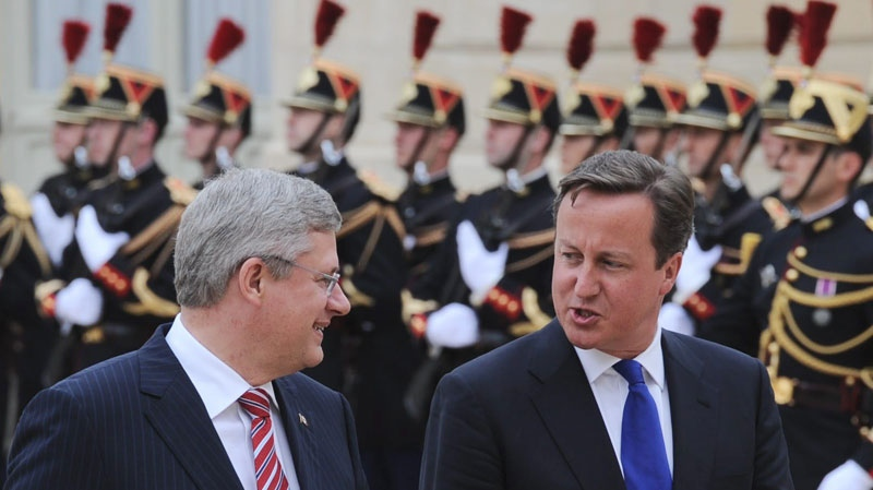 Prime Minister Stephen Harper arrives with British Prime Minister David Cameron to the Palais de l'Elysee in Paris to take part in  talks on Libya on Thursday, Sept. 1, 2011.