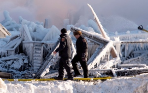 Civil Security officers walk by debris from a fatal fire which destroyed a seniors residence in L'Isle-Verte, Que., Thursday, January 23, 2014. THE CANADIAN PRESS/Jacques Boissinot