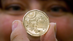 Julie Cossette, of Parks Canada, holds a loonie coin celebrating the centennial of Parks Canada during an event in Richmond, B.C., on Friday October 21, 2011. (THE CANADIAN PRESS/Darryl Dyck)