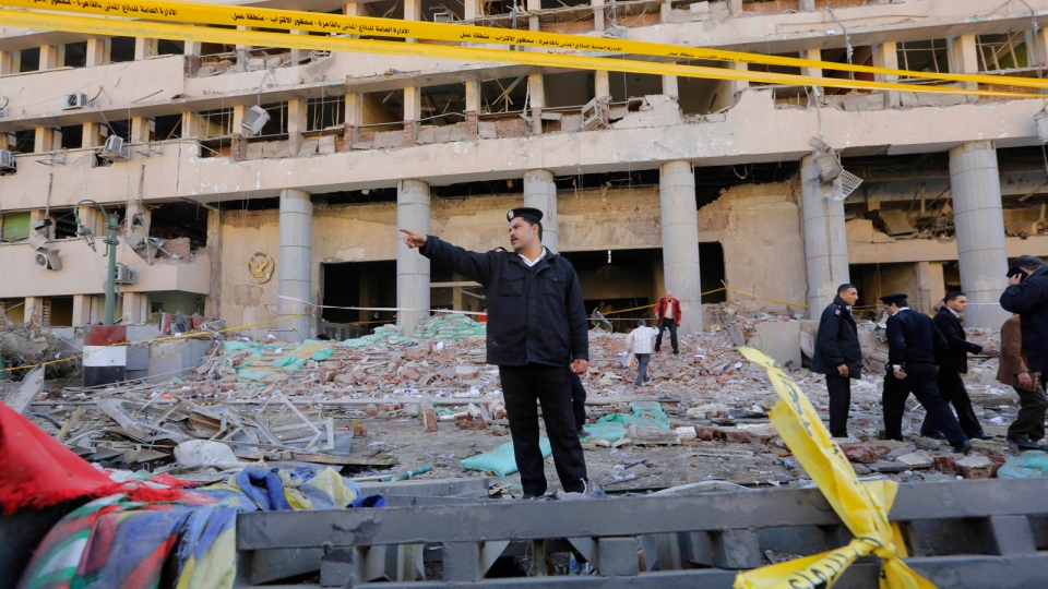 An Egyptian policeman shouts at bystanders to keep away from the site of a blast at the Egyptian police headquarters in downtown Cairo, Egypt, Friday, Jan. 24, 2014. (AP / Amr Nabil)