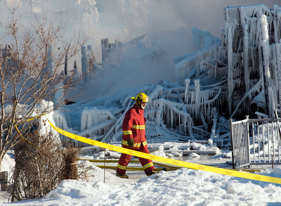 A firefighter walks past the rubble where a deadly fire destroyed a seniors residence Thursday, Jan. 23, 2014, in L'Isle-Verte, Que. (The Canadian Press/Ryan Remiorz)