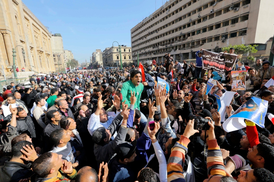 Egyptians shout anti-terrorism slogans as they demonstrate in front the site of a blast at the Egyptian police headquarters, at right, and the Museum of Islamic Art, at left, in downtown Cairo, Egypt, Friday, Jan. 24, 2014. (AP / Amr Nabil)