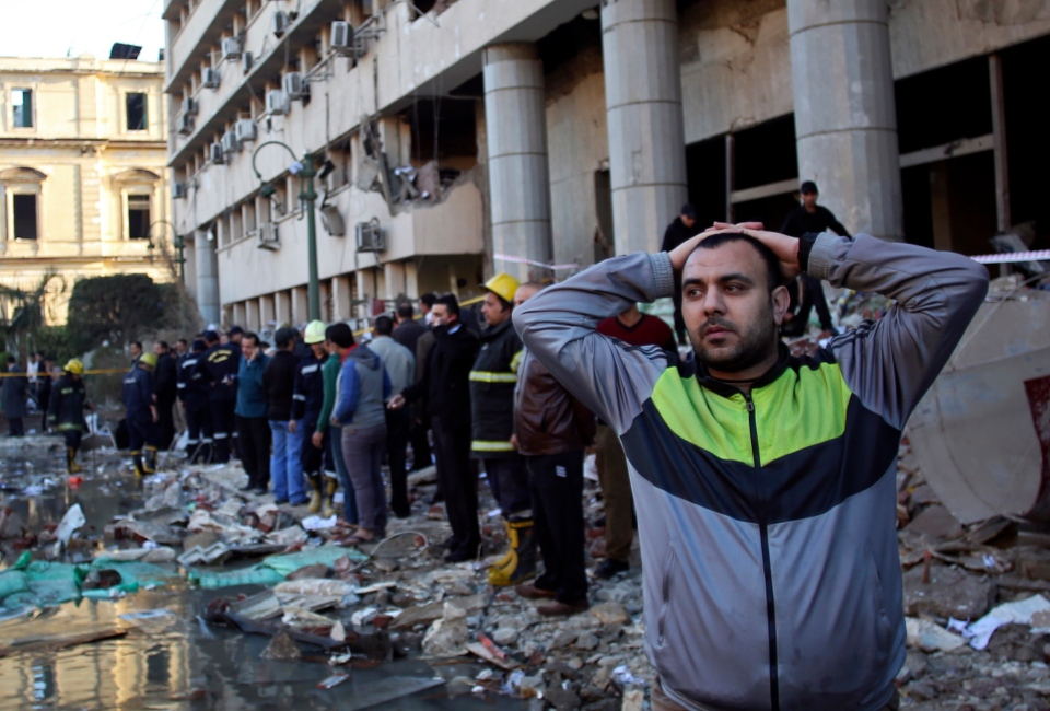 An Egyptian man stands in rubble after an explosion at the Egyptian police headquarters in downtown Cairo, Friday, Jan. 24, 2014. (AP / Khalil Hamra)