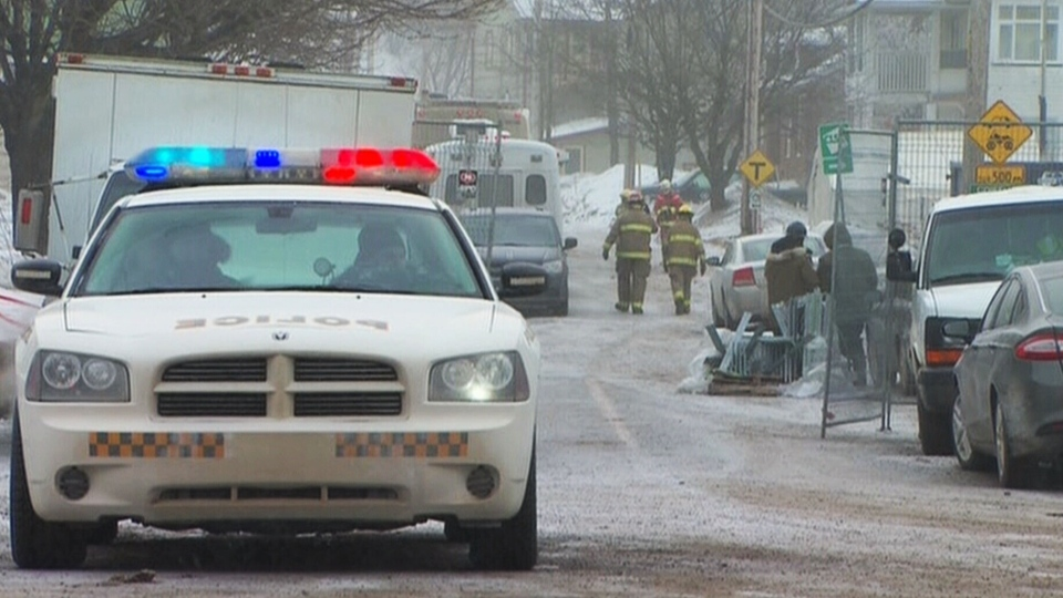 A police vehicle is parked by the frozen rubble of the seniors residence destroyed in a fatal fire in L'Isle-Verte, Que., Friday, Jan. 24, 2014.
