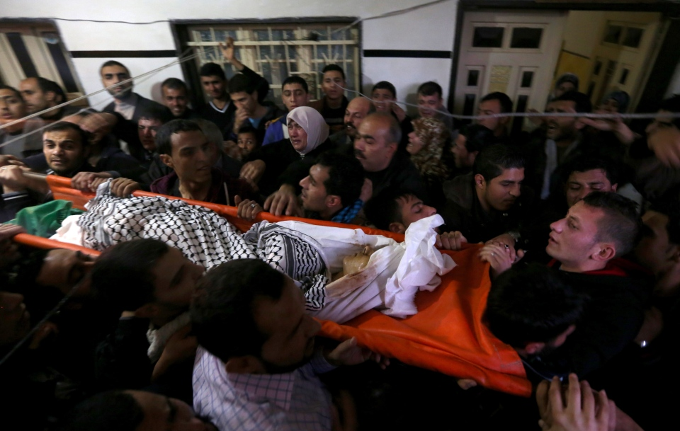 Mourners carry the body of Bilal Aweida, a 20-year-old Palestinian man, during his funeral in Beit Lahiya, northern Gaza Strip, Friday, Jan. 24, 2014.  (AP Photo/Hatem Moussa)