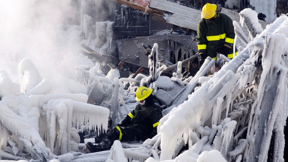 A police investigator slips on the ice as they search through the frozen rubble of a seniors residence in L'Isle-Verte, Que. Friday, Jan. 24, 2014. (Ryan Remiorz / THE CANADIAN PRESS)