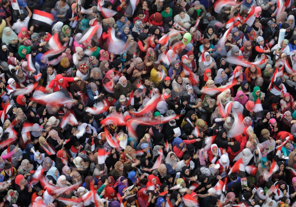 Egyptian women wave nationals flags and posters of Egypt's Defense Minister, Gen. Abdel-Fattah el-Sissi during a pro-military rally marking the third anniversary of the 2011 uprising in Tahrir Square in Cairo, Egypt, Saturday, Jan. 25, 2014. (AP Photo/Amr Nabil)