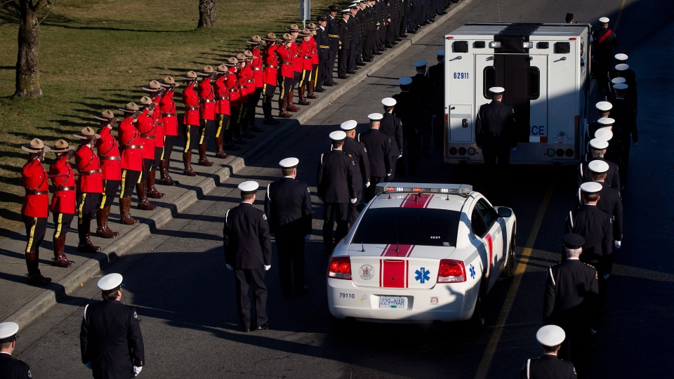 RCMP officers salute as an ambulance carries the ashes of late North Shore Rescue leader Tim Jones while his family follows behind in a car after a ceremony celebrating his life in North Vancouver, B.C., on Saturday, Jan. 25, 2014. (Darryl Dyck / THE CANADIAN PRESS)