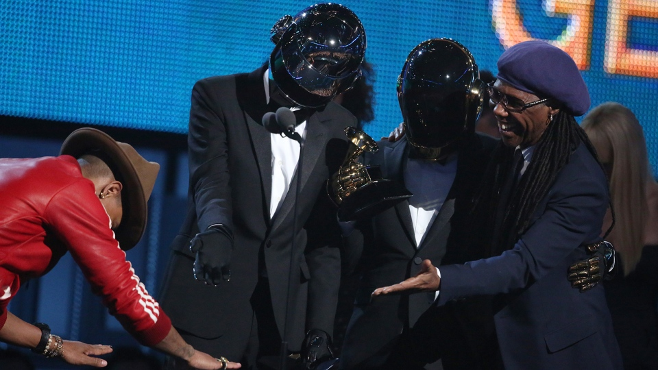 Pharrell Williams, left, presents the award to Thomas Bangalter, second from left, and Guy-Manuel de Homem-Christo of Daft Punk, and Nile Rodgers for best pop duo/group performance for 'Get Lucky' at the 56th annual Grammy Awards at Staples Center on Sunday, Jan. 26, 2014, in Los Angeles. (Matt Sayles / Invision)