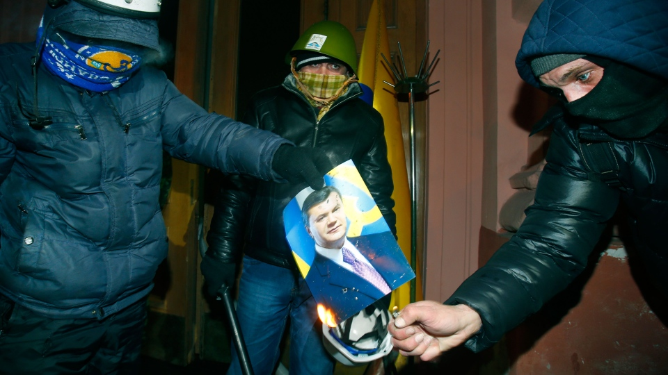 Protesters burn a portrait of President Viktor Yanukovych at the entrance to the Justice Ministry in central Kyiv, Ukraine, early Monday, Jan. 27, 2014. (AP / Sergei Grits)