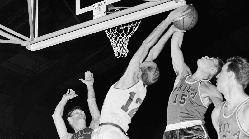 This April 2, 1956, file photo shows George Yardley (12) Fort Wayne outreaching Tom Gola (15) of the Philadelphia Warriors, under his own basket to save the ball for the Pistons in Fort Wayne. (AP Photo/File)