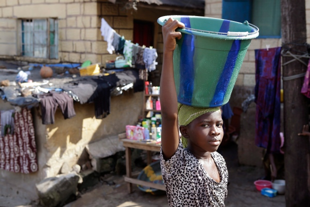 A girl carries water home from a public tap in Freetown, Sierra Leone, Monday, Nov. 19, 2012. (AP Photo/Rebecca Blackwell)