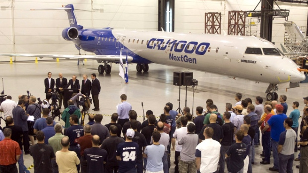 Quebec Premier Jean Charest reacts to Bombardier's approval for the launch of the new CSeries jet, in front of the company's CRJ1000 prototype plane at a news conference in the Bombardier plant in Mirabel, Que., Sunday, July 13, 2008.  (Ryan Remiorz / THE CANADIAN PRESS)