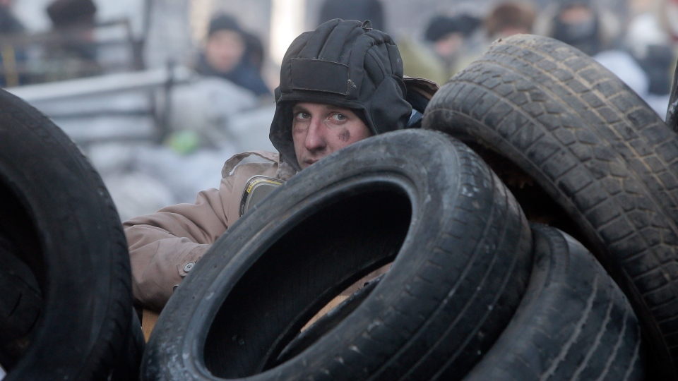 A protester guards the barricades in front of riot police in Kyiv, Ukraine, Monday, Jan. 27, 2014. (AP / Efrem Lukatsky)