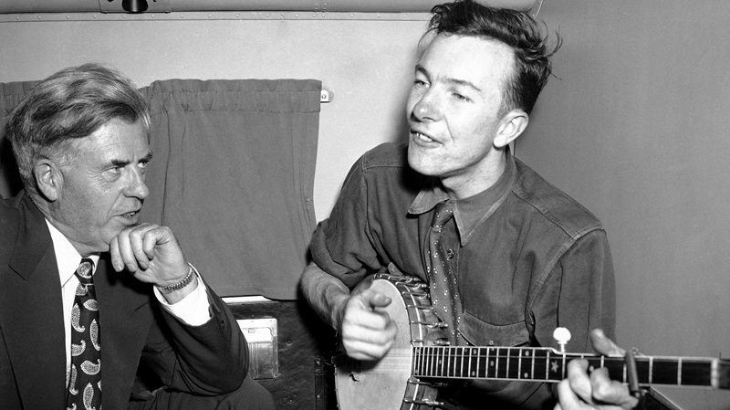 Henry A. Wallace, listening to Pete Seeger, his banjo-playing singer, on a plane between Norfolk and Richmond, Va., Aug. 28, 1948. (AP)