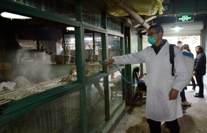A worker disinfects cages at a closed poultry store in Hangzhou in east China's Zhejiang province on Friday, Jan. 24, 2014. (AP Photo)