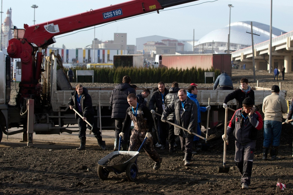 Workers prepare to plant trees along a road near the Olympic Park in Sochi, Russia, Tuesday, Jan. 28, 2014. (AP / Pavel Golovkin)