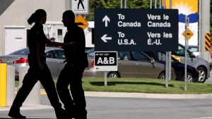 Canadian border guards are silhouetted as they replace each other at an inspection booth at the Douglas border crossing on the Canada-USA border in Surrey, B.C., on Thursday, Aug. 20, 2009. (Darryl Dyck / THE CANADIAN PRESS)