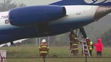 Fire crews work to contain a fuel leak from a United Express plane that skidded off the runway at the Ottawa International Airport Sunday, Sept. 4, 2011.