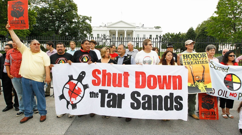 Demonstrators hold up signs in front of the White House in Washington, Friday, Sept. 2, 2011, to protest the Keystone XL Pipeline project in the U.S., and the Tar Sands Development in Alberta Canada. (AP / Luis M. Alvarez)