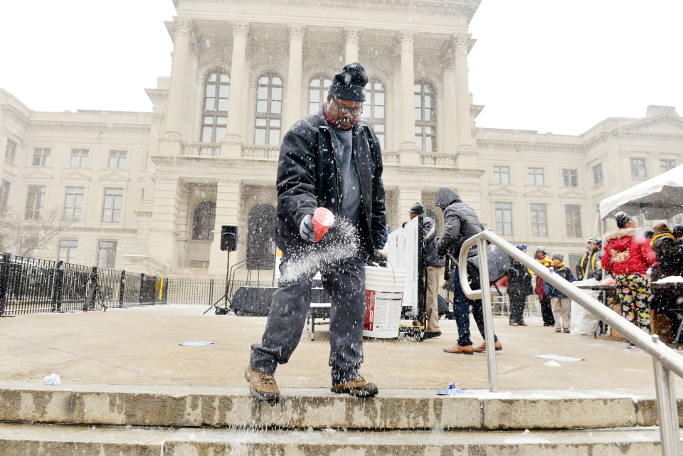 Deon Jackson with the Georgia Building Authority, salts steps in front of the Capitol on Tuesday, Jan. 28, 2014, in Atlanta. Snow falling in Atlanta caused schools to close early and sent workers home at mid-day Tuesday. (AP Photo/Atlanta Journal-Constitution, Kent D Johnson)