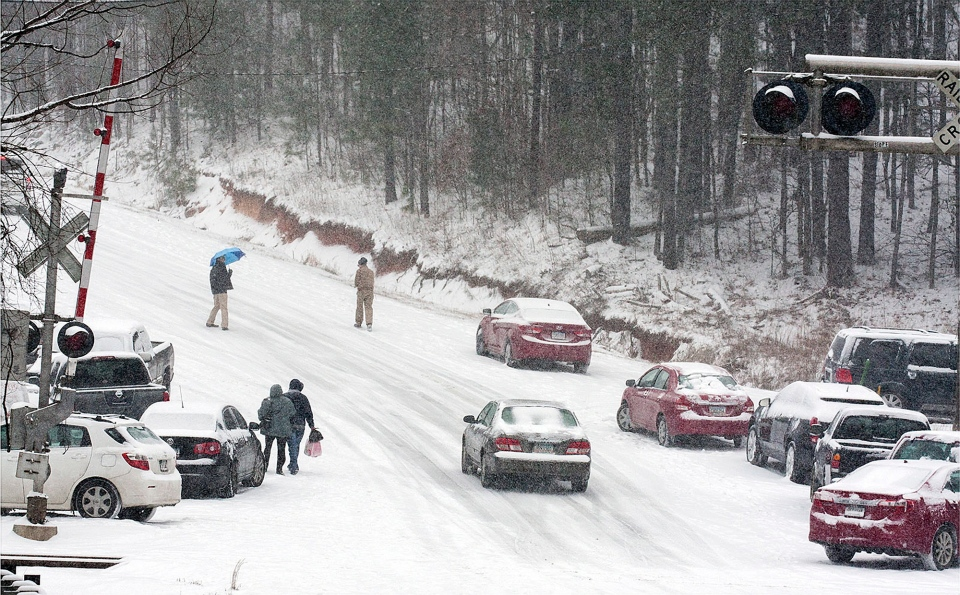 Motorists abandon their vehicles and start walking to their homes on Georgia Highway 140, Tuesday, Jan. 28, 2014 in Canton, Ga. (AP Photo/The Marietta Daily Journal, Kelly J. Huff)