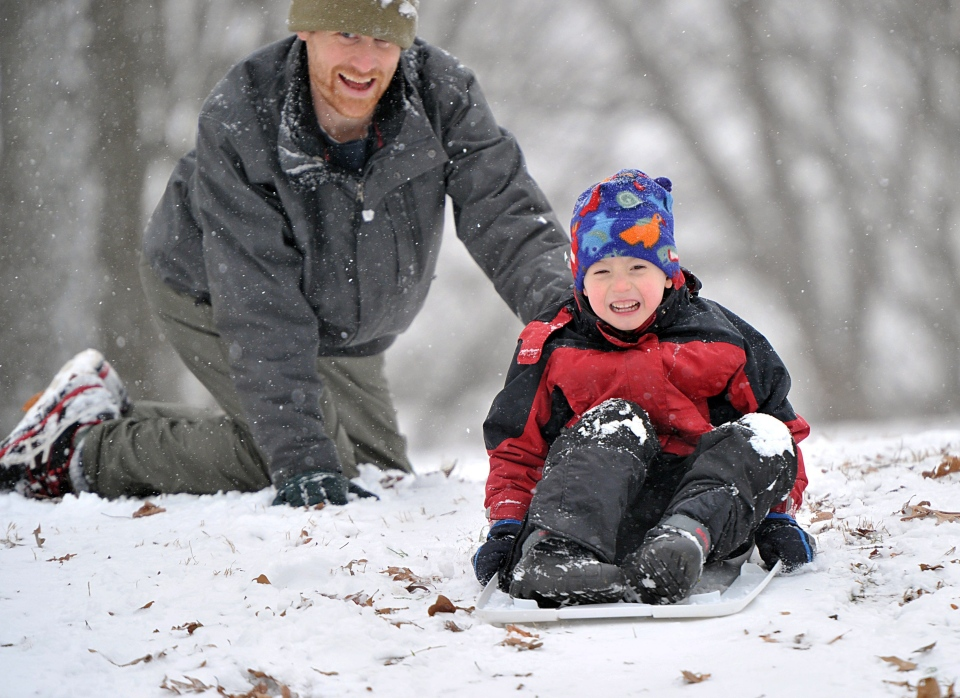 Tim Stevens pushes his 4-year-old son, Sam, down a hill on a sled at Grand Park, Tuesday, Jan. 28, 2014, in Atlanta. (AP Photo/Atlanta Journal-Constitution, Hyosub Shin)