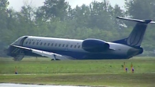 A United Express flight lies in the grass at the Ottawa International Airport after skidding off the runway Sunday, Sept. 4, 2011.