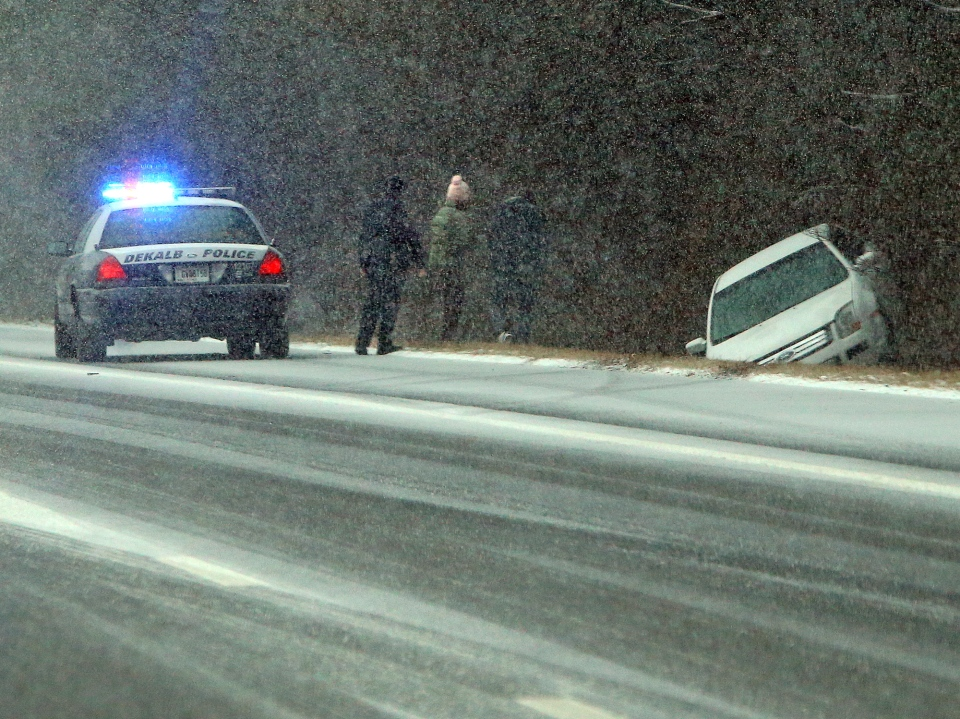 A Dekalb Police officer stops to check on Jesse Hatcher after he says another motorist caused him to lose control of his car and spin into the ditch off I-20 West near Conyers, Georgia, Tuesday, Jan. 28, 2014.(Atlanta Journal-Constitution / Curtis Compton)