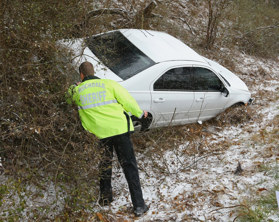 A Rockdale Sheriff deputy checks on a crashed vehicle off Interstate 20 West near Conyers, Ga., Tuesday, Jan. 28, 2014. (Atlanta Journal-Constitution /, Curtis Compton)
