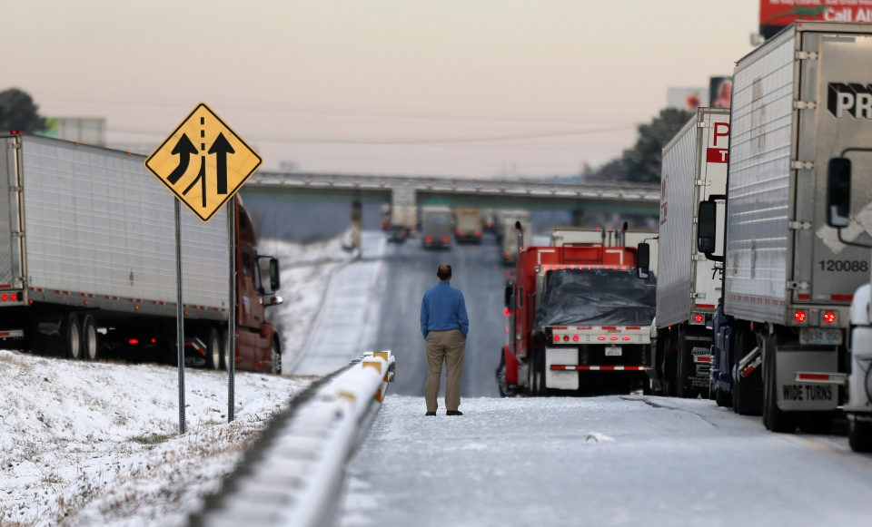 A man stands on the frozen roadway as he waits for traffic to clear along Interstate 75 in Macon, Ga., Wednesday, Jan. 29, 2014. (AP / John Bazemore)