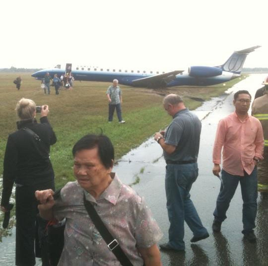 Passengers walk away from their United Express flight after it skidded off the runway at the Ottawa International Airport Sunday, Sept. 4, 2011.